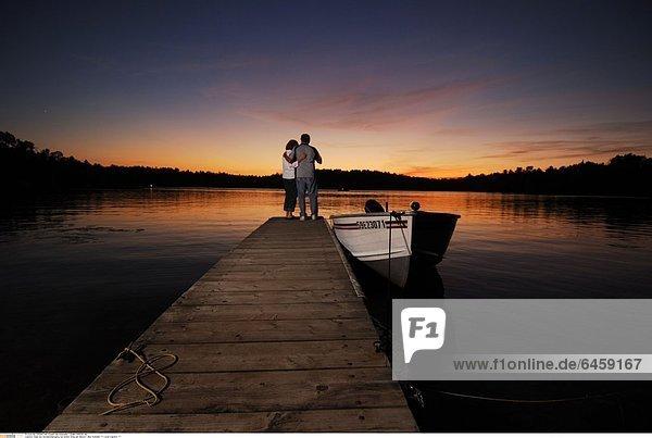 Paar bei Sonnenuntergang auf einem Steg am Moore Lake  Kanada *** Local Caption ***
