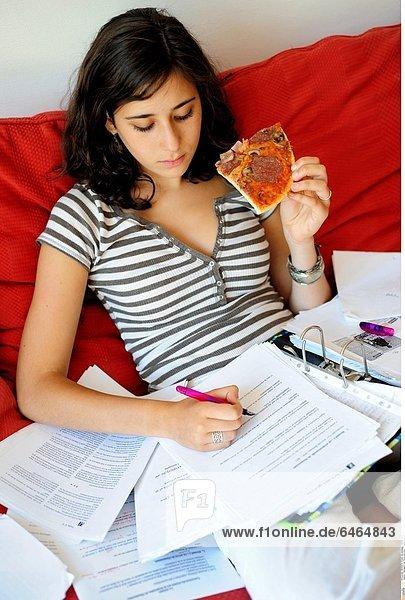Teenagerin isst Pizza und lernt *** Local Caption ***