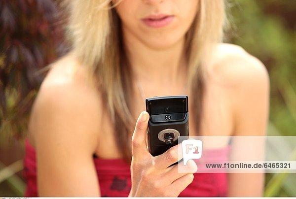 Junge Frau mit ihrem Handy *** Local Caption ***