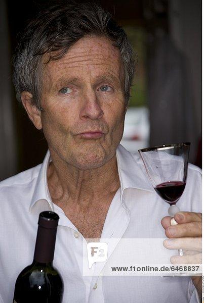 Älterer Mann trinkt ein Glas Rotwein