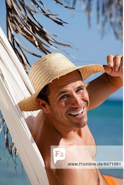 Mann in einer Hängematte am Palmenstrand