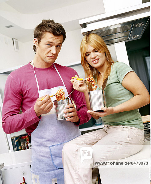 1222470 indoor kitchen people couple woman 20-25 man young dark haired 25-30 blonde long hair pink apron blouse green stand sit eat meal spaghetti pasta hold tin tins mime close up vertical
