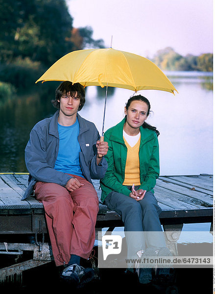 1216669 outdoor lake water pier day spring couple girl woman brunette blouse green trousers orange grey jacket young man boy 20-25 dark haired sit hold yellow umbrella vacation holidays rest relax vertical