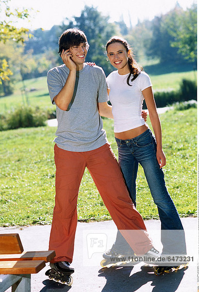1216721 outdoor park day spring couple girl woman brunette long hair grey t-shirt t shirt white blouse jean jeans trousers orange young man boy 20-25 dark haired roller skates skate stand sport recreation smile smiling hold telephone phone cell cellular cellphone mobile call talk speak communication telecommunication vertical