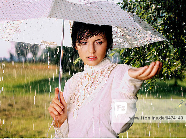 1223056 outdoor day summer park garden people woman young 25-30 brunette fringe portrait close up blouse white lace lacy rain raining raindrop raindrops water umbrella dot dotted wet hair collar catch horizontal