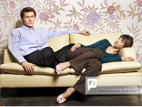 1224708 indoor flat room wall pattern patterns flower flowers woman couple young 20-25 girl brunette long hair man people young 25-30 dark haired sofa couch blouse sweater blue sad sadness lie sit rest relax think dream horizontal