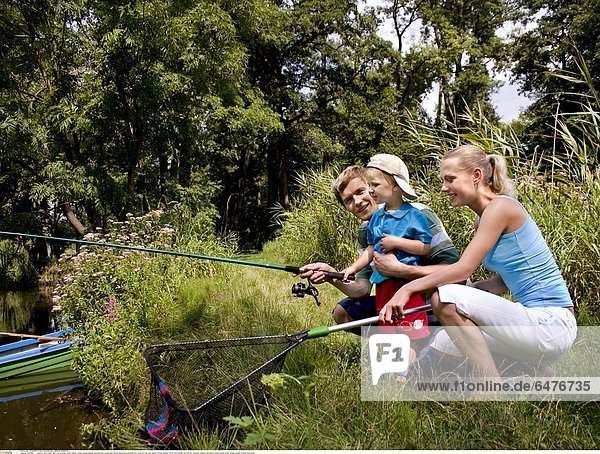 1224899 outdoor park water lake day summer couple family young woman blonde ponytail man young dark haired blouse blue blouses boy child 0-5 cap son father mother parents 25-30 hold fishing rod fish net vacation holdays recreation stand crouch smile smiling profile profiles horizontal