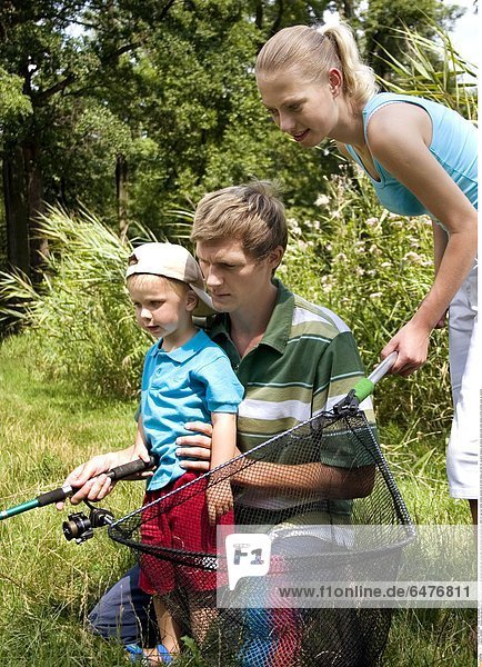 1224898 outdoor park day summer couple family young woman blonde ponytail man young dark haired blouse blue blouses boy child 0-5 cap son father mother parents 25-30 hold fishing rod fish net vacation holdays recreation stand kneel smile smiling profile profiles close up vertical