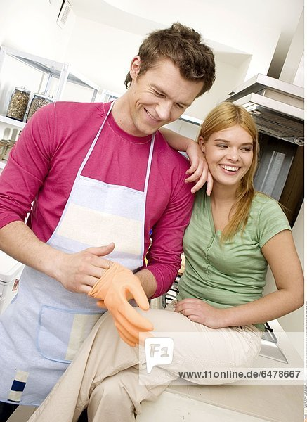 1225496 indoor flat kitchen couple young woman girl 20-25 blonde long hair green blouse man dark haired 25-30 pink blouse apron stand sit glove put on smile smiling close up vertical