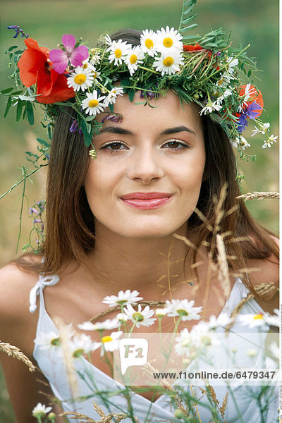 1228756 outdoor day summer people woman girl young 20-25 brunette long haired hair meadow field rest relax vacation blouse white portrait close up flower vertical flowers chaplet smile smiling