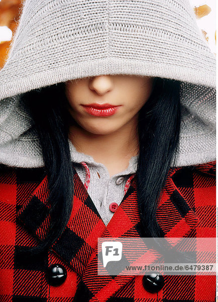 1228853 indoor studio people woman young 25-30 brunette long haired hair fragment face cover sad sadness portrait close up fashion autumn hood grey jacket pane paned red black make up lip lips vertical
