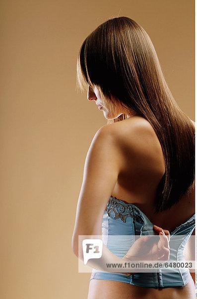 1228681 indoor studio people woman young 25-30 brunette long hair vertical lacy fringe corset blue fasten button unbutton close up