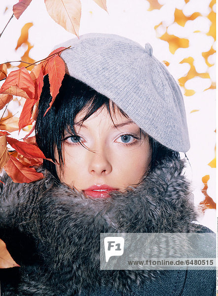 1228810 indoor studio people woman young 25-30 brunette fringe portrait close up fashion autumn coat grey make up lip lips vertical leaf leaves orange cap fur collar