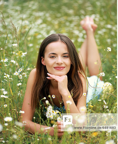 1228741 outdoor day summer people woman girl young 20-25 brunette long haired hair meadow field rest relax vacation smile smiling lie vertical