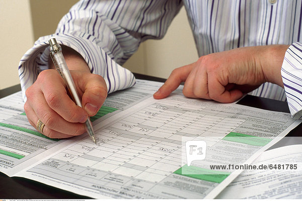1217885 indoor flat kitchen man fragment sit chemise stripe striped close up paper papers document documents tear tax return tax returns fill account for accounts write pen hand hands horizontal