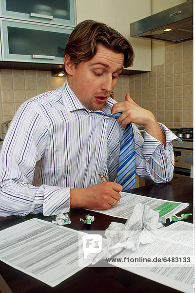 1217896 indoor flat kitchen man 35-40 mature whitey sit chemise stripe striped tie close up paper papers document documents tear tax return tax returns fill account for accounts stress emotions think vertical