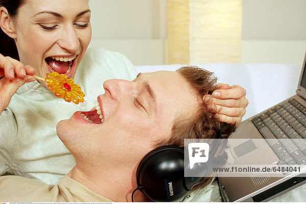 1218821 indoor bed bedroom flat room woman man young 25-30 fair haired brunette lie personal computer notebook communication internet rest relax eye eyes close hobby music listen headphones eat flower shape lollipop sweets smile smiling joy emotions horizontal
