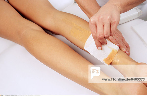 1221915 indoor parlour beauty woman fragment lie naked nakedness body beautician beauty care cosmetic cosmetology depilation depilate wax tear off leg close up horizontal
