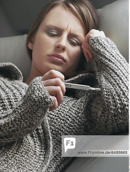 1221079 indoor flat room young woman 25-30 brunette grey sweater lie sofa couch hold thermometer fever temperature look read ill disease illness cold resist hand close up vertical