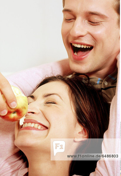 1218811 indoor flat room man woman couple young 25-30 brunette fair haired sit rest relax close up portrait smile smiling eat apple hold eye eyes close diet health bit emotions joy feed embrace rest relax vertical