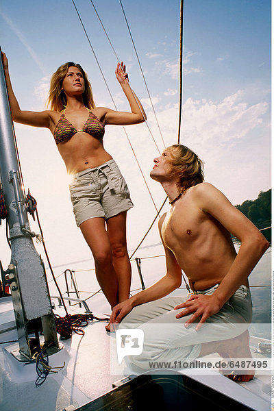 1233501 outdoor water lake day summer people couple young woman man girl boy 20-25 blonde long hair fair haired shorts bikini swimsuit stand crouch body sailing boat sailingboat look vacation holidays recreation sailing yachting profile vertical