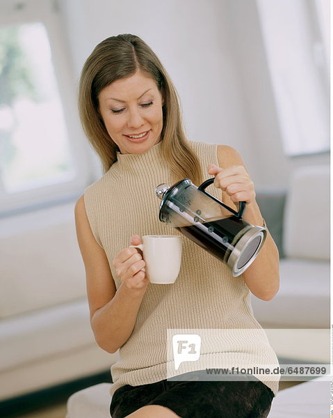 1228862 indoor flat room people woman young 25-30 smile smiling long haired brunette sweater beige sit drink coffee hold percolator mug vertical