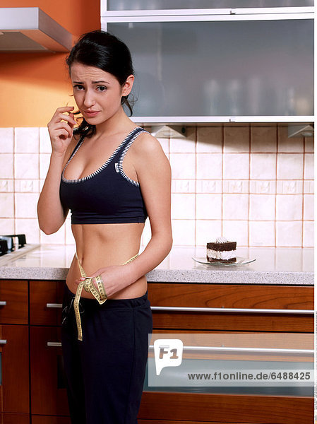 1235891 indoor flat kitchen people woman young 25-30 brunette stand close up blouse black trousers hold mime measure diet slim sweets cake vertical stomach navel