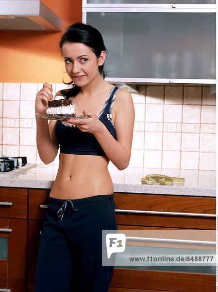 1235909 indoor flat kitchen people woman young 25-30 brunette stand close up blouse black trousers hold plate eat smile smiling sweets cake vertical stomach navel