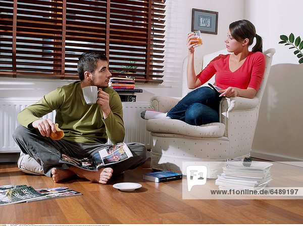 1234425 indoor flat room people couple young woman girl brunette 20-25 long hair ponytail sit floor armchair man dark haired 25-30 beard barefoot foot feet eat sandwich drink hold mug glass juice food read newspaper magazine horizontal