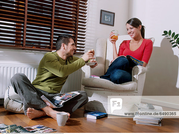 1234427 indoor flat room people couple young woman girl brunette 20-25 sit floor armchair man dark haired 25-30 beard barefoot foot feet eat sandwich drink hold mug glass juice food read newspaper magazine smile smiling horizontal