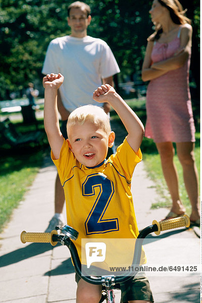 1236495 outdoor summer park spring day people child boy 0-5 fair haired rest relax blouse yellow sit ride bike close up mother brunette woman young 25-30 long vertical blur father family man couple 30-35 dark stand dress pink blouses white