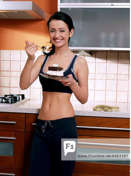 1235908 indoor flat kitchen people woman young 25-30 brunette stand close up blouse black trousers hold plate eat smile smiling sweets cake vertical stomach navel