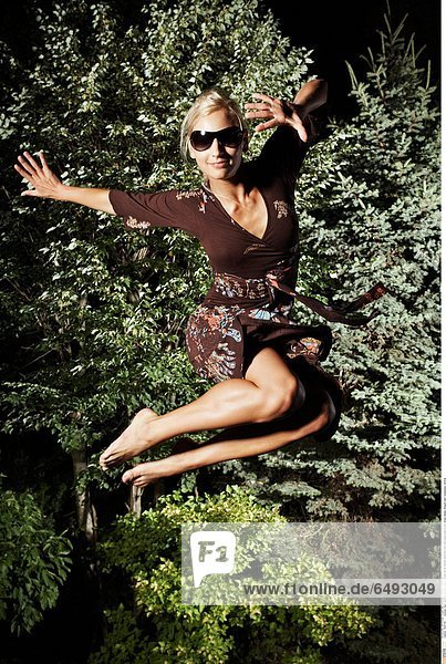 1235745 outdoor night summer people young woman 25-30 blonde barefoot foot feet jump pose brown dress design designs dark sunglasses vertical