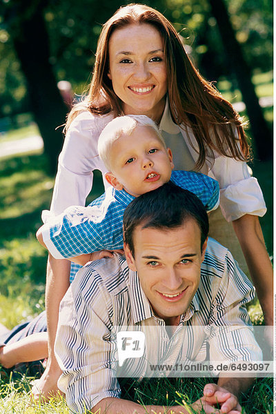 1236505 outdoor summer spring day people man young dark haired 30-35 father son child 0-5 fair rest relax blouse blue white blouses play fun family mother woman brunette long vertical lie smile smiling