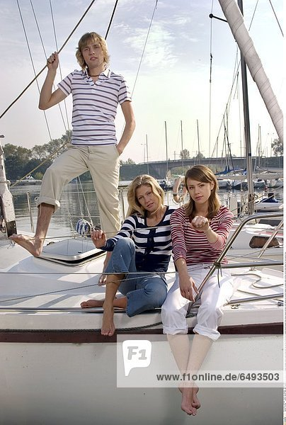 1237089 outdoor marina water lake evening summer people friend friends friendship young woman women girls man girl boy 20-25 blonde brunette blouse blouses stripe stripes striped red black white sailing boat vacation holidays recreation sailing yachting vertical smile smiling foot feet barefoot day