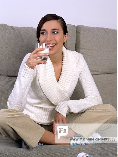 1239370 indoor flat room sit rest relax sofa people woman brunette young 20-25 girl sweater white trousers beige drink milk smile smiling glass hold vertical