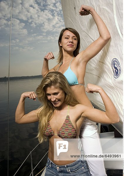 1237117 outdoor day marina water lake evening summer people young woman girl 20-25 brunette sailing boat sailing boat vacation holidays recreation sailing yachting smile smiling close up bikini trousers jean jeans white embrace friend friends friendship women girls pose vertical