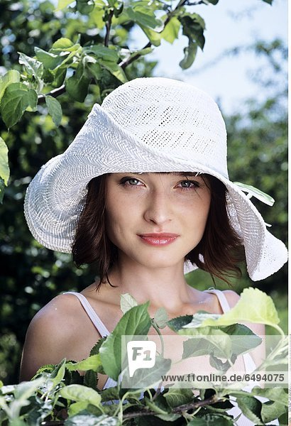 1236869 outdoor summer day people woman young 20-25 girl brunette fringe blouse white portrait close up vertical smile smiling hat