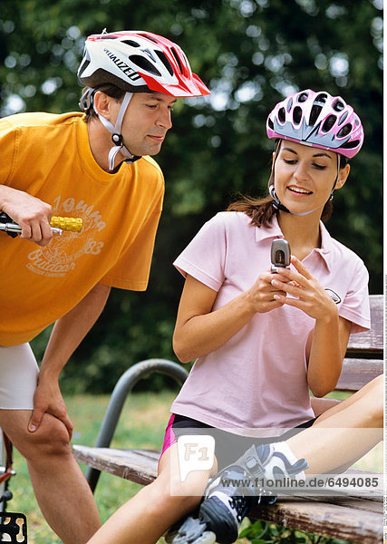 1239289 outdoor day summer vacation people woman young 20-25 girl smile smiling blouse pink shorts black park relax rest sport helmet sit bench vertical hold hand telephone mobile phone cell cellular cellphone communication telecommunication close up sms mms read send write bike couple man dark haired helmets blouses orange vertical 25-30