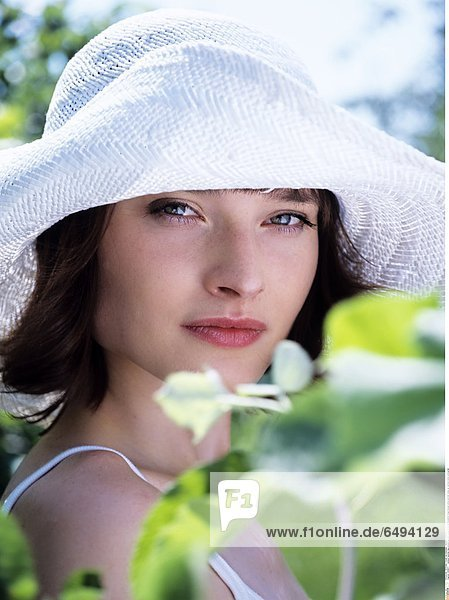 1236877 outdoor summer day people woman young 20-25 girl brunette fringe blouse white portrait close up vertical smile smiling hat