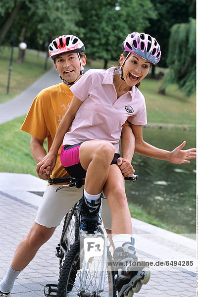 1239287 outdoor day summer vacation people woman young 20-25 girl smile smiling blouse pink shorts black park relax rest sport helmet vertical couple man dark haired helmets blouses orange ride bike mime emotions scream sit water lake 25-30