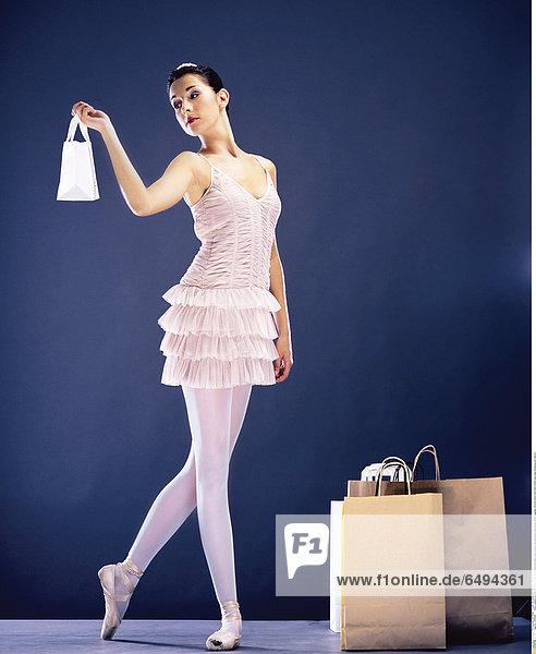 1236962 indoor people woman brunette young 25-30 ballerina ballet dance show representation play dress white leggings vertical stand hold hand hands bag bags shopping bun dancer