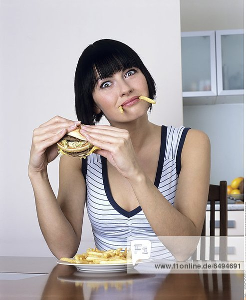 1239119 indoor flat kitchen people woman young girl 20-25 brunette fringe blouse white stripe stripes striped eat plate hamburger fast food chip chips vertical smile smiling close up portrait mime fun play