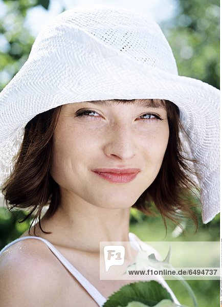 1236880 outdoor summer day people woman young 20-25 girl brunette fringe blouse white portrait close up vertical smile smiling hat
