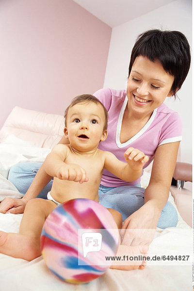 1239166 indoor flat room people boy girl child 0-5 baby blonde fair haired white sheet sit stand mother motherhood smile smiling naked nakedness woman young 25-30 brunette blouse pink vertical ball hold play fun embrace
