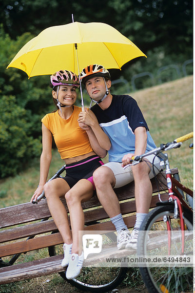 1239295 outdoor day summer vacation people woman young 20-25 girl smile smiling blouse orange shorts black park relax rest sport helmet sit bench man couple dark haired helmets hold yellow umbrella fun play vertical blouses blue bike bikes ride 25-30