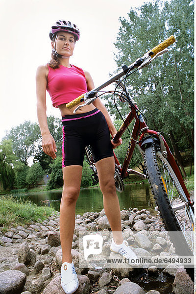 1239279 outdoor day summer vacation people woman young 20-25 girl smile smiling blouse pink shorts black relax rest sport helmet vertical ride bike water lake pebble pebbles