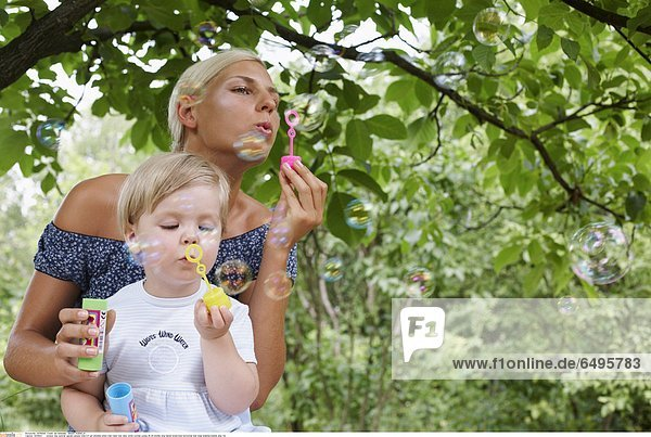 1243654 outdoor day summer garden people child 0-5 girl blondes white tree trees rest relax white woman young 25-30 blonde long haired dress blue horizontal hold soap bubbles bubble play fun