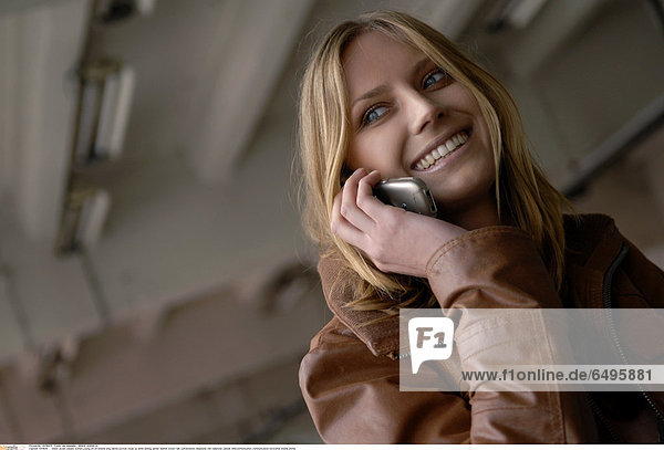 1241839 indoor studio people woman young 20-25 blonde long haired portrait close up smile smiling jacket leather brown talk conversation telephone cell cellphone cellular telecommunication communication horizontal mobile phone