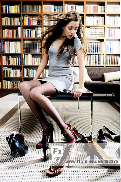 1244002 indoor flat table sit room people woman young girl 20-25 brunette long haired rest relax blouse grey skirt tights black shoe shoes vertical bookcase bookcases book books sit table